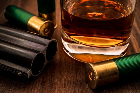 A glass of whiskey and a double-barreled shotgun with ammo