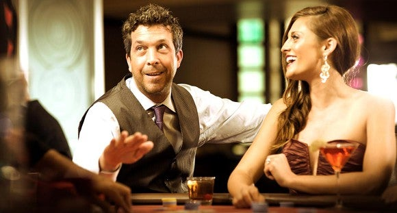 A man and woman playing tables games at the Meadows resort, a Pinnacle-owned casino.