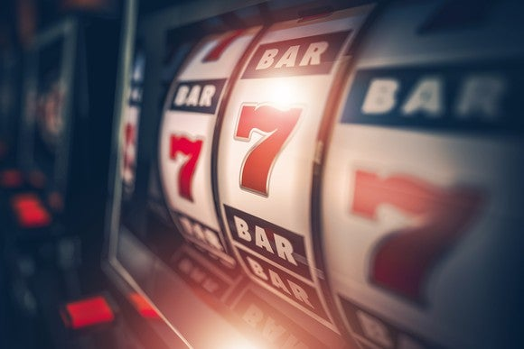 A slot machine slows to nearly land on three 7's in a row.