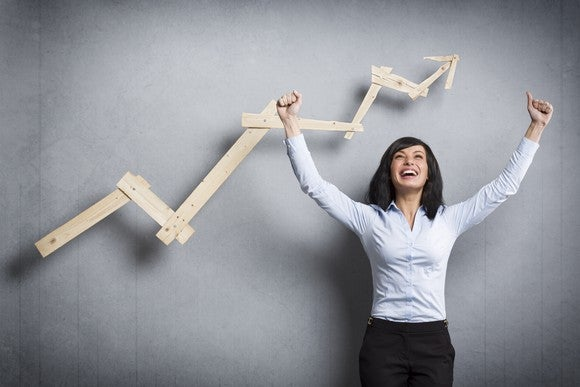 A jubilant young woman celebrating in front of a rising stock chart.