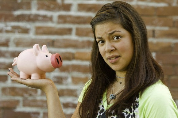 A young adult confused by her piggy bank, implying a lack of millennial savings.