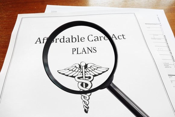 A magnifying glass hovering over an Affordable Care Act policy.