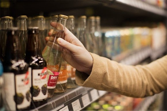 A person grabs a bottle off of a grocery shelf at an Amazon Go store in Seattle.