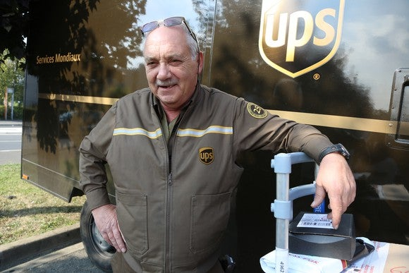 A UPS employee standing in front of a delivery truck.