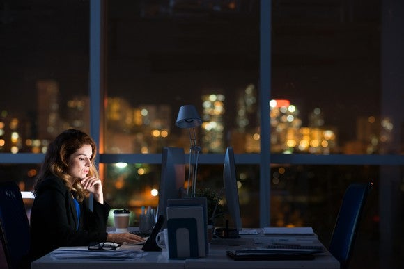 A woman working at her office late into the night.