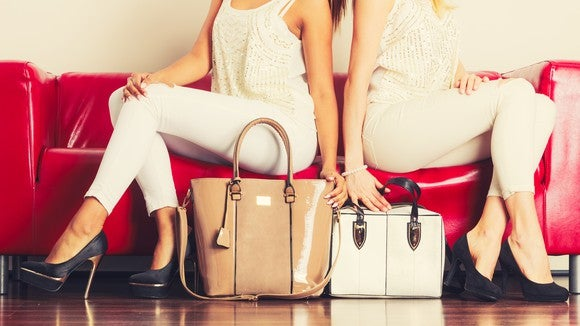 Two women sit on a couch with their purses at their feet.