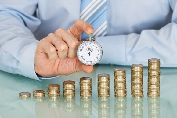 An man's hand holding a stopwatch in front of progressively larger stacks of coins.