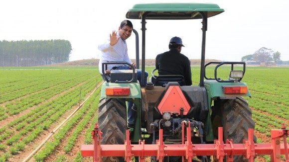 A microsoft employee rides on the back of a tractor in India.