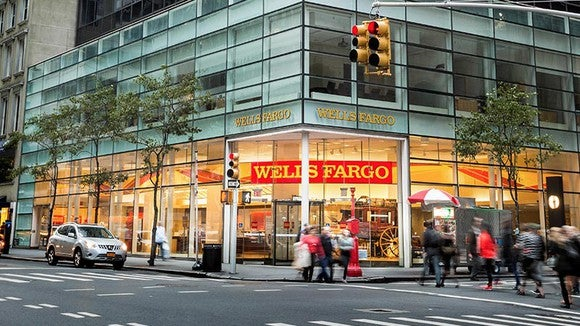 A group of people walk past a Wells Fargo store front.