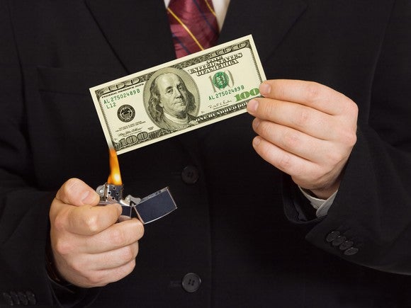 Man in business suit lighting a $100 bill with a lighter