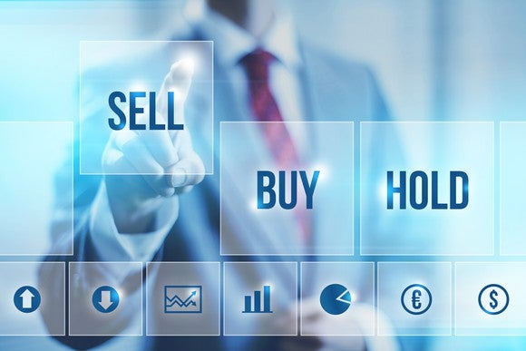 "Man pointing to ""sell"" on a screen showing the options ""buy,"" ""sell,"" and ""hold."""