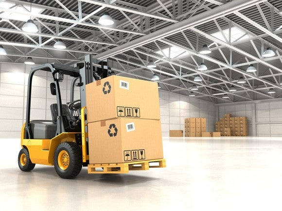 Picture of a forklift driving in a large warehouse.