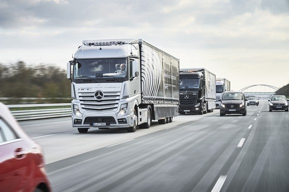 "A self-driving ""platoon"" of 3 Mercedes-Benz tractor-trailers are shown on a highway."