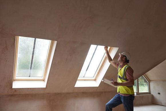 Home inspector checking attic windows