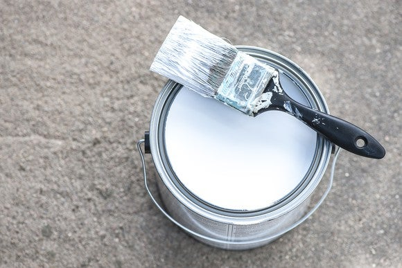Can of white paint with paintbrush.