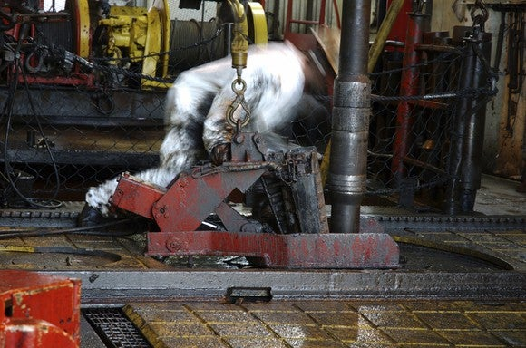 An offshore oil worker connecting a drilling pipe on a rig platform