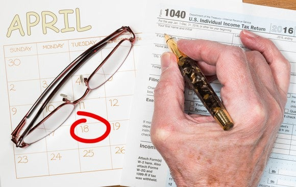A hand holding a pen over a tax form, next to a pair of glasses and April 18 circled on a calendar.