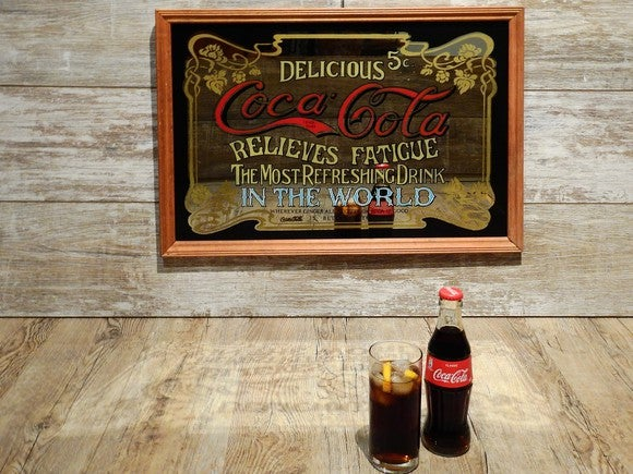 Two Coke bottles sitting in front of a old-time sign describing Coke's benefits.
