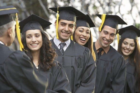 College students at graduation in cap and gown.