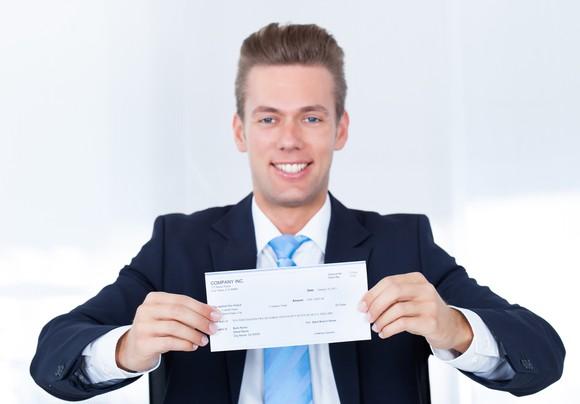 Businessman holding a check.