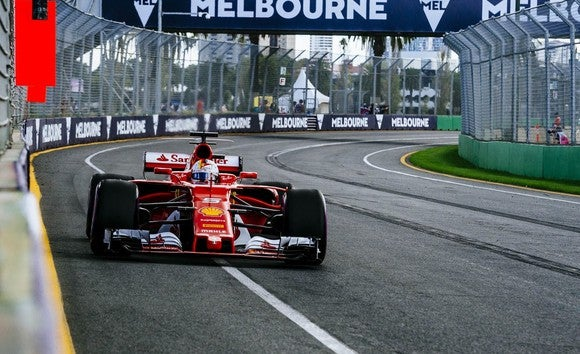 A Ferrari Formula One race car at speed on a racing track.