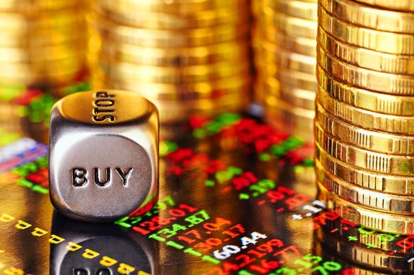 "A die showing the word ""buy,"" beside stacks of gold coins."