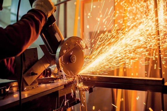 Sparks fly from a cutting tool in a manufacturing facility.