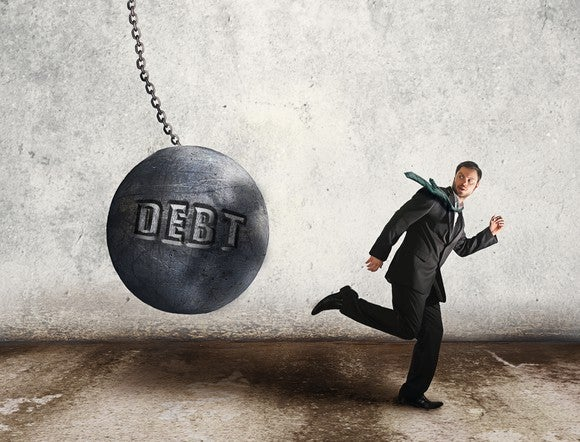 "Wrecking ball with ""debt"" written on it, swinging towards businessman."