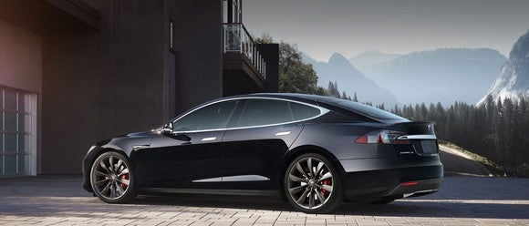 Black Tesla model S parked in front of house with mountains in background.