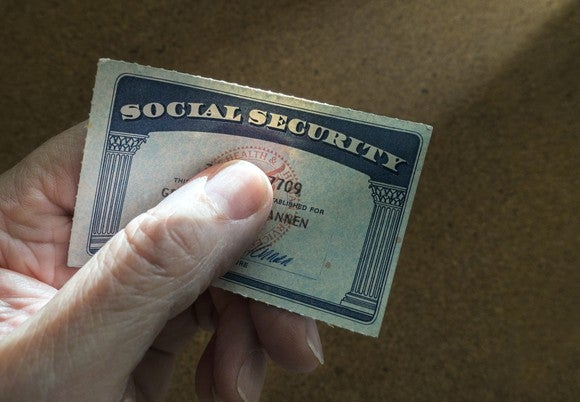 A senior holding a Social Security card.