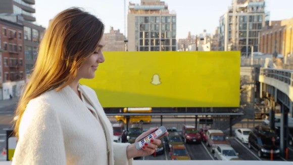 A Snapchat bllboard, behind a woman looking at a smartphone.