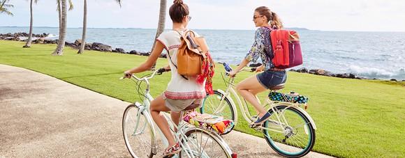 Two young women riding bikes along a beach, each wearing a Vera Bradley backpack.