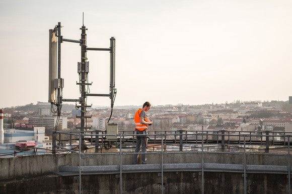 A telecom worker tests a mobile phone company's cell tower on the top of a building.
