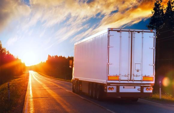 Truck driving into sunrise.
