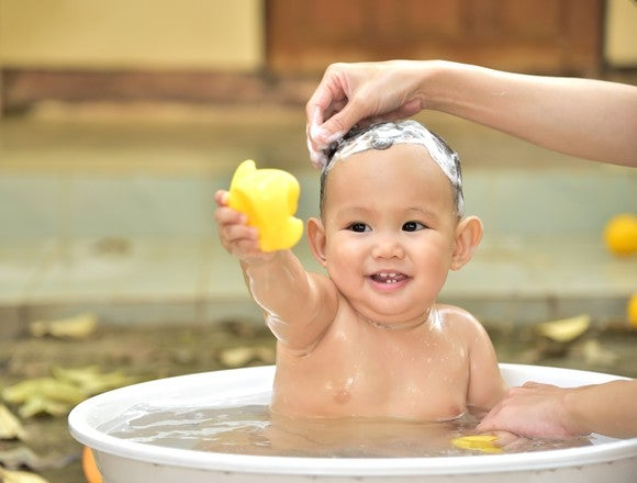 A baby in a bathtub having its hair washed.