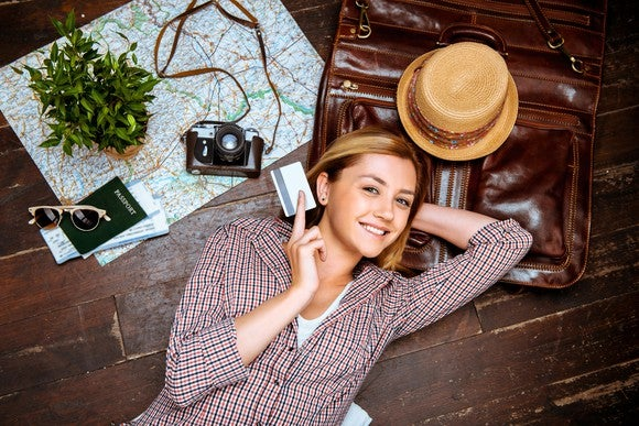 Young woman smiling, holding credit card. Passport, tickets, vintage camera, hat, and map are on floor.