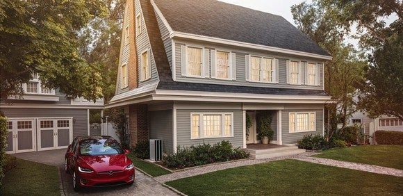 Home with Tesla solar tiles and a Model X parked in the driveway