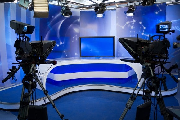 Two TV cameras point toward a stage in a news studio