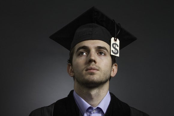 A college grad with a dollar sign as the tassel on his graduation cap.