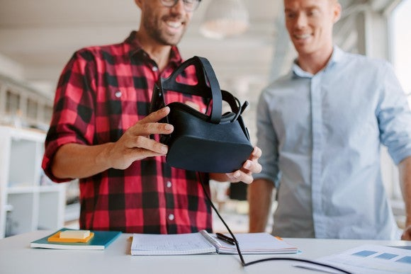 Two guys looking at a virtual reality headset.