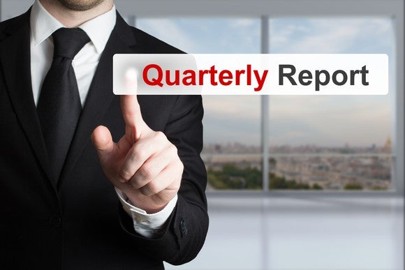 "A man in a suit pointing to the words ""Quarterly report"" on a digital screen."