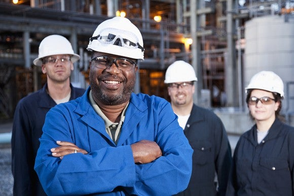 Employees of a petrochemical facility pose for a photo.