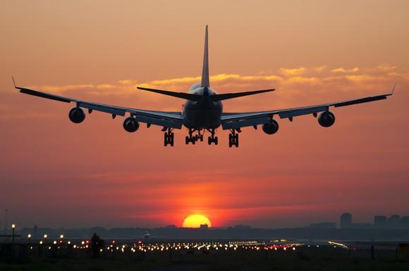 A plane landing at sunset.