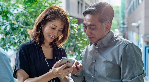 Business man and woman looking at a mobile device