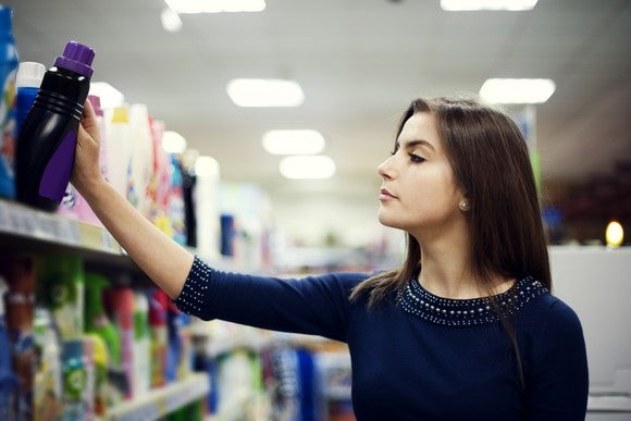 A woman looking at laundry detergent in a store
