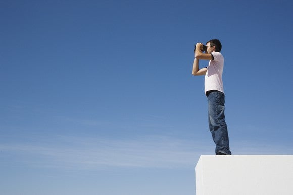Man staring in a pair of binoculars.