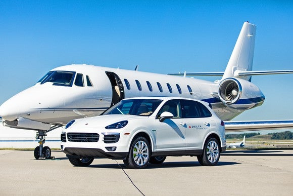 A private jet is behind a Porsche SUV used by Delta Private Jets for transporting customers.