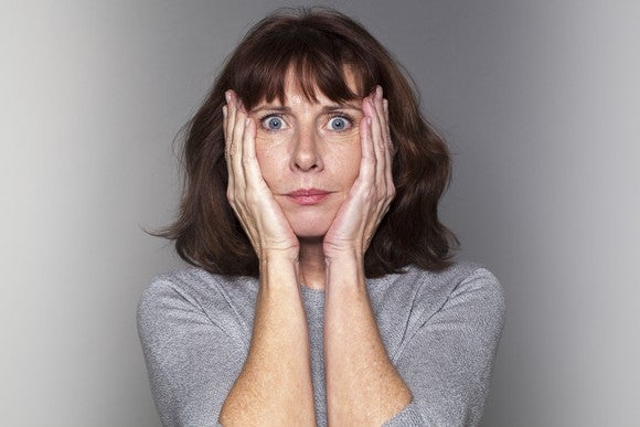 A woman clasps her palms to her cheeks.