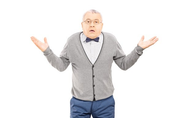 A senior man in a vest and bowtie shrugging his shoulders and raising his arms.