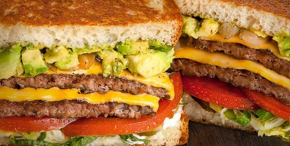 A close up of a burger from the Habit, which is served on grilled bread and with tomatoes and avocado.
